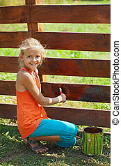Young girl painting a wooden fence