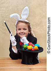 Happy magician girl making easter eggs with her powers -...
