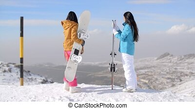 Two women snowboarders enjoying the winter view from a snowy...
