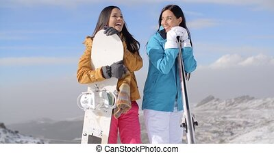 Two young woman with their snowboards - Two attractive happy...