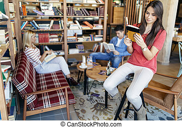 Beautiful woman reading book and preparing for exam