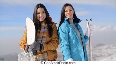 Two gorgeous young women posing with snowboards on a snowy...
