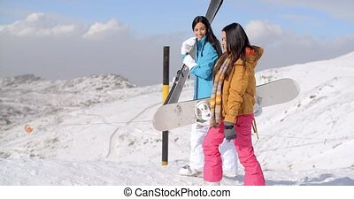 Two friends hiking up ski slope - Two smiling beautiful...