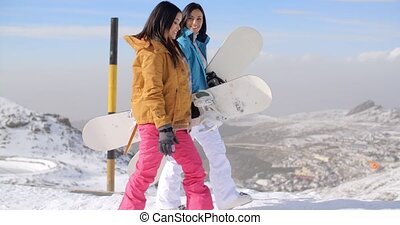 Two women carrying their snowboards on a mountaintop at a...
