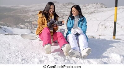 Two young female snowboarders enjoying a chat as they sit...
