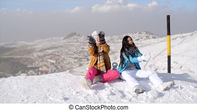 Two young women having fun in winter snow as they sit at the...