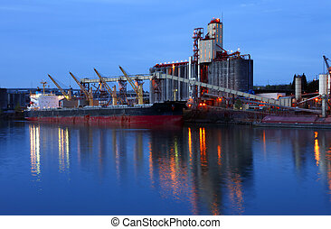 Grain elevators and cargo ship at dusk - Grain elevator and...