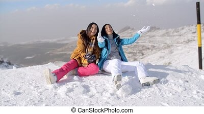 Two young women frolicking in the snow as they sit on a...