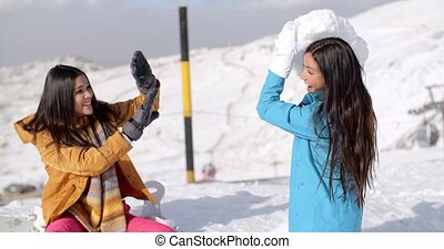 Two young female friends playing in the snow threatening to...