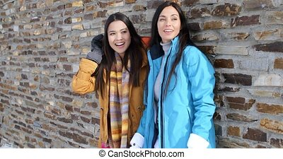 Laughing twins in jackets and glove near wall - Adorable...