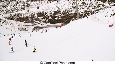 View from a ski lift of skiers below on a run at the ski...