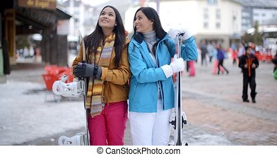 Two gorgeous young brunette snowboarders standing close...