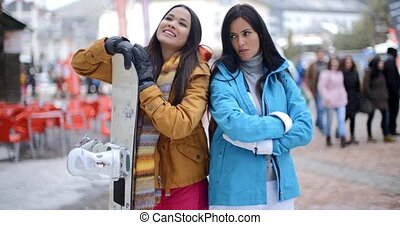 Skiers with snowboard and folded arms - Two female twin...