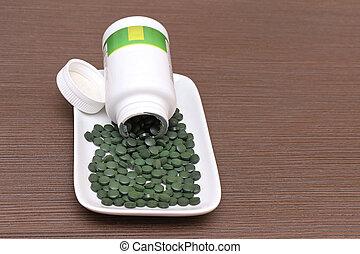 Spirulina plate - Spirulina super food tablets flowing out...