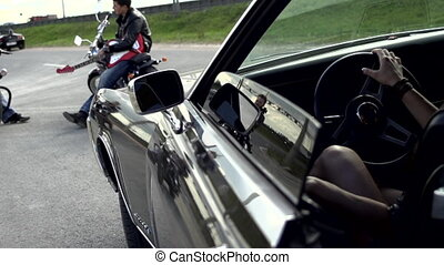 Young girl sitting in the Buick Riviera and closing door in...