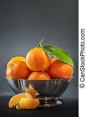Clementines in bowl - Clementines with leaf in metallic bowl...