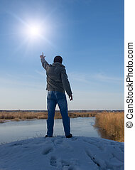 Man in front of the sun holding the hands up