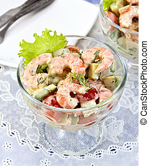 Salad with shrimp and tomatoes in glass on table