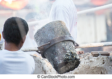 Worker pouring molten metal to casting Buddha statue