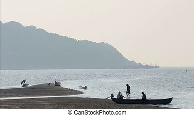 Misty tropical seascape with boats and fishermen silhouettes...