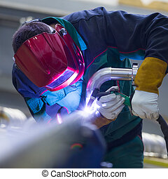 Industrial worker welding in metal factory. - Industrial...