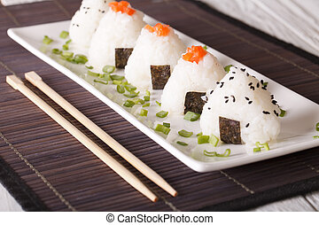 Japanese onigiri stuffed with salmon and sesame close-up....