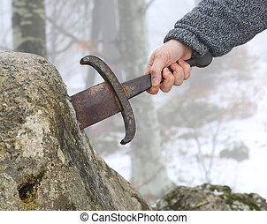 knight tries to remove Excalibur sword in the stone - Hand...