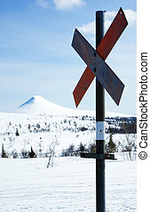 Ski trail marker - A rusty ski trail marker against a snow...