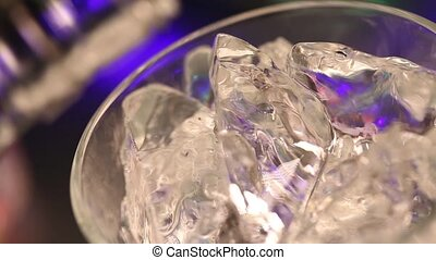 Pouring scotch whiskey into a glass with ice cubes close-up