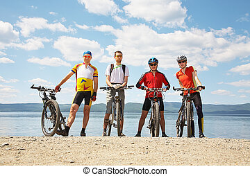 men with bike on a mountain lake