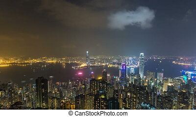 Hong Kong city skyline timelapse at night with Victoria Harbor and skyscrapers illuminated by lights over water viewed from mountain top.