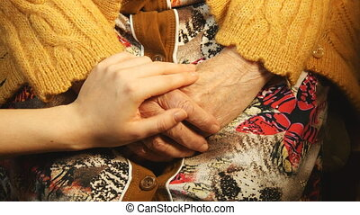 A young hand comforting a old pair of hands