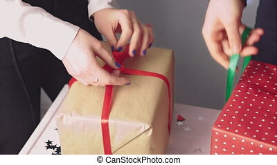 Packing gifts in boxes tied with colorful ribbons