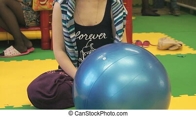 Girl has a yoga with a large rubber ball on the floor in the...