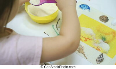 Little girl plays a intelligent game with semolina - Little...