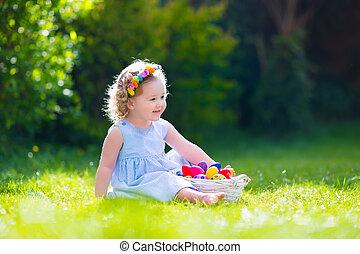 Little girl on Easter egg hunt - Funny little girl playing...