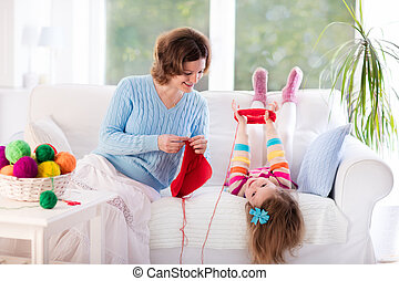 Mother and daughter knitting woolen scarf. Mom teaching...