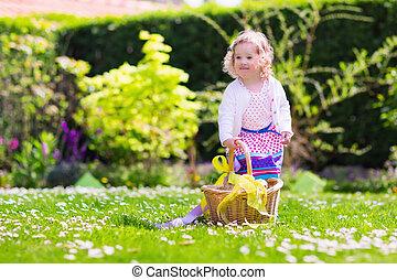 Little girl on Easter egg hunt - Little girl playing in...
