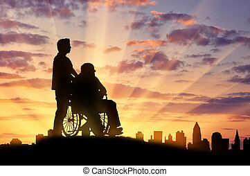 Silhouette of man looking after disabled person - Concept of...