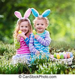 Children on Easter egg hunt - Kids on Easter egg hunt in...