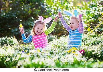 Kids on Easter egg hunt in blooming spring garden. Children...