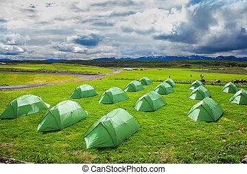 Campground in Iceland Green tent on a grassy lawn