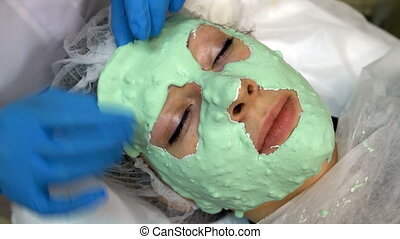 Doctor making off cosmetic mask on face of caucasian woman