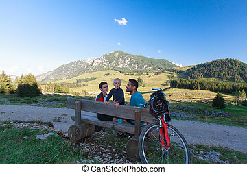 Young family resting - Young family resting on the bench on...