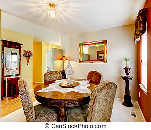 Dinning room with red accent wall, carpet, and detailed wooden table.