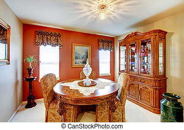 Small dining room with red accent wall, and detailed old world style furniture.