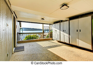 Large open covered garage storage area with closets and rock floor.