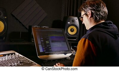 sound man designer in his recording studio - tracking shot -...