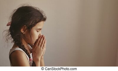 girl teen praying on a black background - woman praying on a...