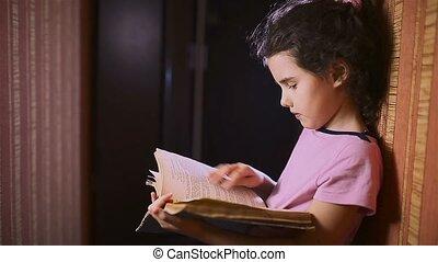 teen girl reading a book is a wall indoor - teen girl...